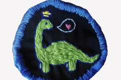 Hand-embroidered-dinosaur-patch-on-black.