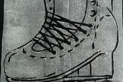 Lino-printed-Get-your-skates-on-patch-white-on-black-close-up