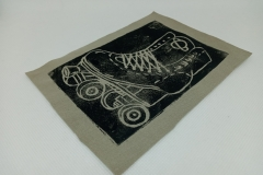 Lino-printed-Get-your-skates-on-patch-black-on-beige.